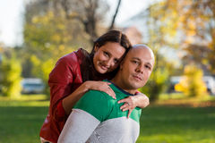 Męski przewożenie Uśmiecha się kobiety Na Jego Z powrotem Przy parkiem Obrazy Stock
