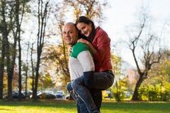 Męski przewożenie Uśmiecha się kobiety Na Jego Z powrotem Przy parkiem Obraz Royalty Free