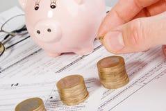 Męski ręki kładzenia pieniądze na dorośnięcie monety stercie Obraz Royalty Free