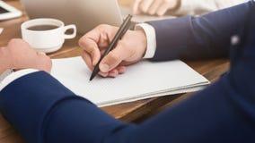 Męski ręki mienia pióro przygotowywający robić notatce w rozpieczętowanym notatniku Fotografia Stock