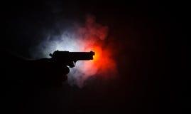 Męski ręki mienia pistolet na czarnym tle z dymem barwił z powrotem światła, Mafijny zabójcy pojęcie (żółty pomarańczowej czerwie Zdjęcie Royalty Free