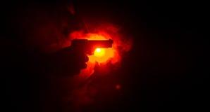 Męski ręki mienia pistolet na czarnym tle z dymem barwił z powrotem światła, Mafijny zabójcy pojęcie (żółty pomarańczowej czerwie Obraz Stock