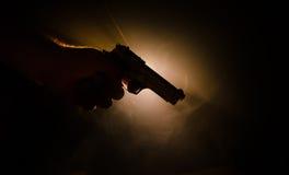 Męski ręki mienia pistolet na czarnym tle z dymem barwił z powrotem światła, Mafijny zabójcy pojęcie (żółty pomarańczowej czerwie Obrazy Royalty Free