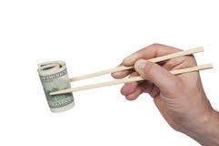 Męski ręki mienie z chopsticks rolka sto dolarów Obraz Royalty Free