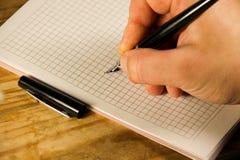 Męski ręki writing używać fontanny pióro na notatniku Obraz Stock