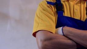 Męski repairman w błękitnych coveralls pokazuje aprobaty i krzyżuje ręki na klatce piersiowej zbiory wideo