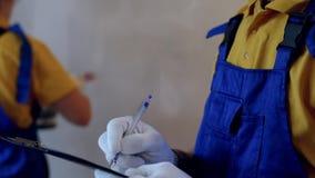 Męski repairman w błękitnych coveralls robi notatkom podczas gdy żeński malarz maluje ścianę z białym kolorem zdjęcie wideo