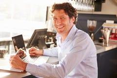 Męski restauracyjny kierownik pracuje na laptopie fotografia stock