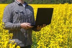 Męski rolnik - biznesmen trzyma laptop na polu żółty kwitnący canola, zakończenie Zdjęcie Stock