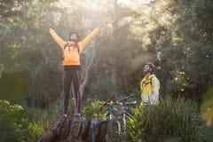 Męski rowerzysta patrzeje żeńską rowerzysta pozycję z rękami up Zdjęcie Royalty Free