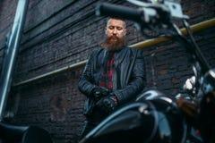 Męski rowerzysta w skórzanej kurtce stawia dalej rękawiczki obraz stock