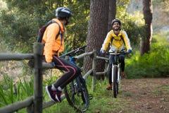 Męski rowerzysty kolarstwo podczas gdy żeński rowerzysty obsiadanie na ogrodzeniu Obraz Royalty Free