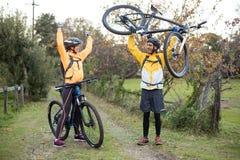 Męski rowerzysty przewożenia rower górski podczas gdy żeński rowerzysta rozwesela on Zdjęcie Royalty Free