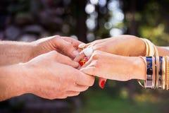 Męski ` s wręcza mieniu żeńskie ` s ręki z czerwonymi gwoździami Zdjęcia Royalty Free