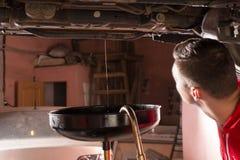 Męski samochodowy mechanik w jednolitym dopatrywaniu jak olej płynie out i Chan Fotografia Royalty Free
