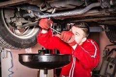 Męski samochodowy mechanik w jednolitym działaniu pod podnoszącym samochodem i Zdjęcia Royalty Free