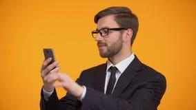 Męski scrolling smartphone i ono uśmiecha się przy kamerą, pożytecznie biznesowy zastosowanie zbiory
