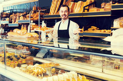 Męski sklepowy asystent demonstruje świeżego wyśmienicie ciasto wewnątrz piec Fotografia Royalty Free