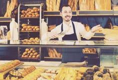 Męski sklepowy asystent demonstruje świeżego wyśmienicie ciasto wewnątrz piec Obrazy Stock