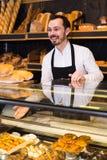 Męski sklepowy asystent demonstruje świeżego wyśmienicie ciasto wewnątrz piec Zdjęcie Stock