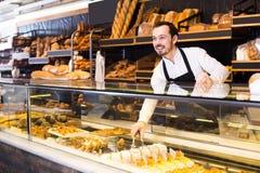 Męski sklepowy asystent demonstruje świeżego wyśmienicie ciasto wewnątrz piec Fotografia Stock