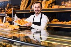 Męski sklepowy asystent demonstruje świeżego wyśmienicie ciasto wewnątrz piec Zdjęcia Royalty Free