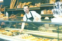 Męski sklepowy asystent demonstruje świeżego wyśmienicie ciasto wewnątrz piec Obraz Stock
