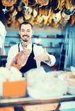 Męski sklepowy asystent demonstruje kawałek mięso w butcher's s Zdjęcia Royalty Free
