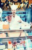 Męski sklepowy asystent demonstruje kawałek mięso w butcher's s Zdjęcia Stock