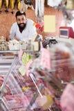 Męski sklepowy asystent demonstruje kiełbasy Fotografia Royalty Free