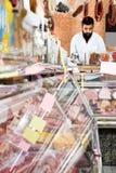 Męski sklepowy asystent demonstruje mięso Obrazy Stock