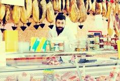 Męski sklepowy asystent demonstruje mięso Zdjęcia Stock