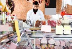 Męski sklepowy asystent demonstruje mięso Zdjęcie Royalty Free