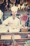 Męski sklepowy asystent demonstruje pokrojonego bekon w butcher's sh Zdjęcie Stock