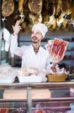 Męski sklepowy asystent demonstruje pokrojonego bekon w butcher's sh Obraz Royalty Free