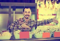 Męski sklepowy asystent demonstruje rodzaje mięso w sklepie Zdjęcie Stock