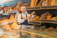 Męski sklepowy asystent demonstruje wyśmienicie bochenki chleb w b Zdjęcia Stock