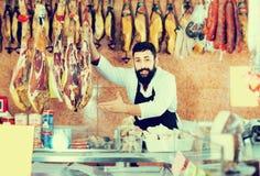 Męski sklepowy asystent pokazuje Hiszpańskiego jamon Zdjęcie Stock