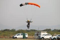 Męski skydiver przybycie wewnątrz dla lądować na trawie z otwartym jaskrawy Obraz Stock