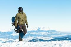 Męski snowboarder trzyma jego deskę w ręce i bierze spacer przy wierzchołkiem góra Obraz Stock