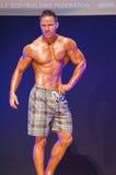 Męski sprawność fizyczna model pokazuje jego budowę ciała w swimsuit om scenie Zdjęcie Royalty Free