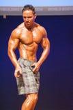 Męski sprawność fizyczna model pokazuje jego budowę ciała w swimsuit om scenie Obraz Royalty Free