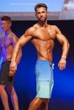 Męski sprawność fizyczna model pokazuje jego budowę ciała w swimsuit om scenie Zdjęcia Royalty Free