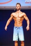 Męski sprawność fizyczna model pokazuje jego budowę ciała w swimsuit om scenie Obraz Stock