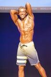 Męski sprawność fizyczna model pokazuje jego budowę ciała w swimsuit om scenie Obrazy Royalty Free