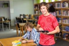 Męski student collegu używa cyfrową pastylkę w bibliotece Zdjęcia Royalty Free