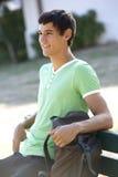 Męski studenta collegu obsiadanie Na ławce Z plecakiem Zdjęcie Stock