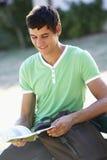 Męski studenta collegu obsiadanie Na ławka Czytelniczym podręczniku Zdjęcia Royalty Free