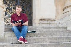 Męski studenta uniwersytetu obsiadanie Na krokach I czytanie Na zewnątrz Bui Zdjęcia Stock