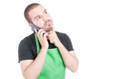 Męski supermarketa pracownik robi myślącemu gestowi przy telefonem Zdjęcie Royalty Free